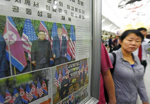 People walk past the display of local newspaper reporting the meeting between North Korean leader Kim Jong Un and U.S. President Donald Trump, at a subway station in Pyongyang, North Korea Wednesday, June 13, 2018. The series of photos on the front page of the ruling workers' party newspaper showed something North Koreans never would have imagined just months ago, their leader Kim warmly shaking hands with Trump. (Minoru Iwasaki/Kyodo News via AP)