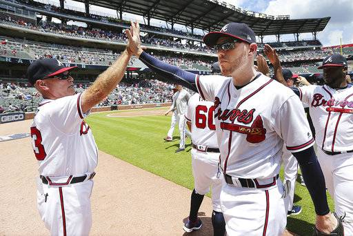 Atlanta Braves' Freedie Freeman, right foreground, gets a high five from manager Brian Snitker after the Braves defeated the New York Mets 2-0 in a baseball game in Atlanta, Wednesday, June 13, 2018. (Curtis ComptonAtlanta Journal-Constitution via AP)