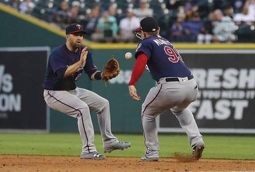 A single hit by Detroit Tigers' Leonys Martin falls between Minnesota Twins second baseman Brian Dozier, left, and first baseman Logan Morrison (99) during the fifth inning of a baseball game, Wednesday, June 13, 2018, in Detroit.