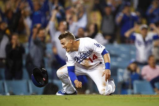 Los Angeles Dodgers' Enrique Hernandez celebrates after scoring on a throwing error by Texas Rangers relief pitcher Matt Bush during the 11th inning of a baseball game, Wednesday, June 13, 2018, in Los Angeles. The Dodgers won 3-2 in the 11th inning.