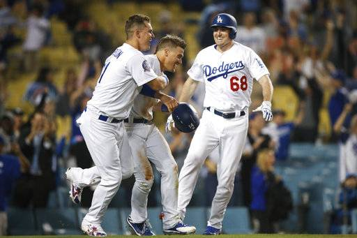 Los Angeles Dodgers' Enrique Hernandez, center, is congratulated by Joc Pederson, left, and Ross Stripling after scoring a game-winning run on a throwing error by Texas Rangers relief pitcher Matt Bush during the 11th inning of a baseball game, Wednesday, June 13, 2018, in Los Angeles. The Dodgers won 3-2.