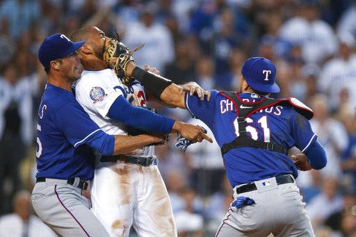 Texas Rangers starting pitcher Cole Hamels, left, restrains Los Angeles Dodgers' Matt Kemp as Kemp scuffles with Rangers catcher Robinson Chirinos during the third inning of a baseball game Wednesday, June 13, 2018, in Los Angeles.
