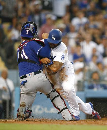 Los Angeles Dodgers' Matt Kemp, right, shoves Texas Rangers catcher Robinson Chirinos while trying to score on a single hit by Enrique Hernandez during the third inning of a baseball game Wednesday, June 13, 2018, in Los Angeles.