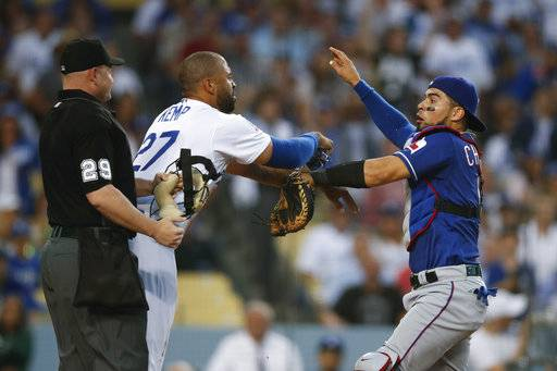Los Angeles Dodgers' Matt Kemp, left, and Texas Rangers catcher Robinson Chirinos scuffle after Chirinos was shoved by Kemp at home plate during the third inning of a baseball game, Wednesday, June 13, 2018, in Los Angeles.