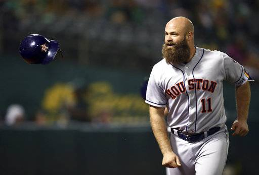 Houston Astros' Evan Gattis flips his helmet after hitting a home run off Oakland Athletics' Danny Coulombe during the seventh inning of a baseball game Wednesday, June 13, 2018, in Oakland, Calif.