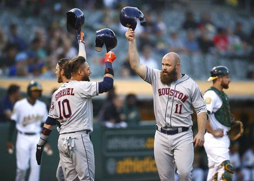 Houston Astros' Evan Gattis, right, celebrates with Yuli Gurriel (10) and Josh Reddick, left, after hitting a three-run home run off Oakland Athletics' Emilio Pagan during the second inning of a baseball game Wednesday, June 13, 2018, in Oakland, Calif.