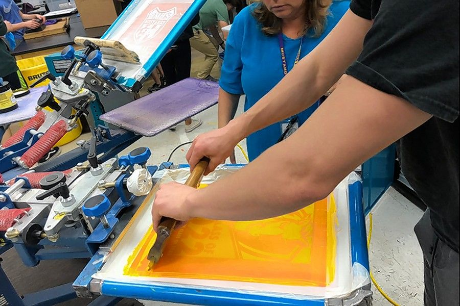Students make spirit shirts on screen printing machines in the Rolling Meadows High School graphic arts studio.