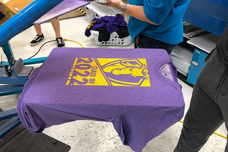 A Rolling Meadows High School Class of 2022 spirit shirt created in-house has a newly applied gold Mustang logo.