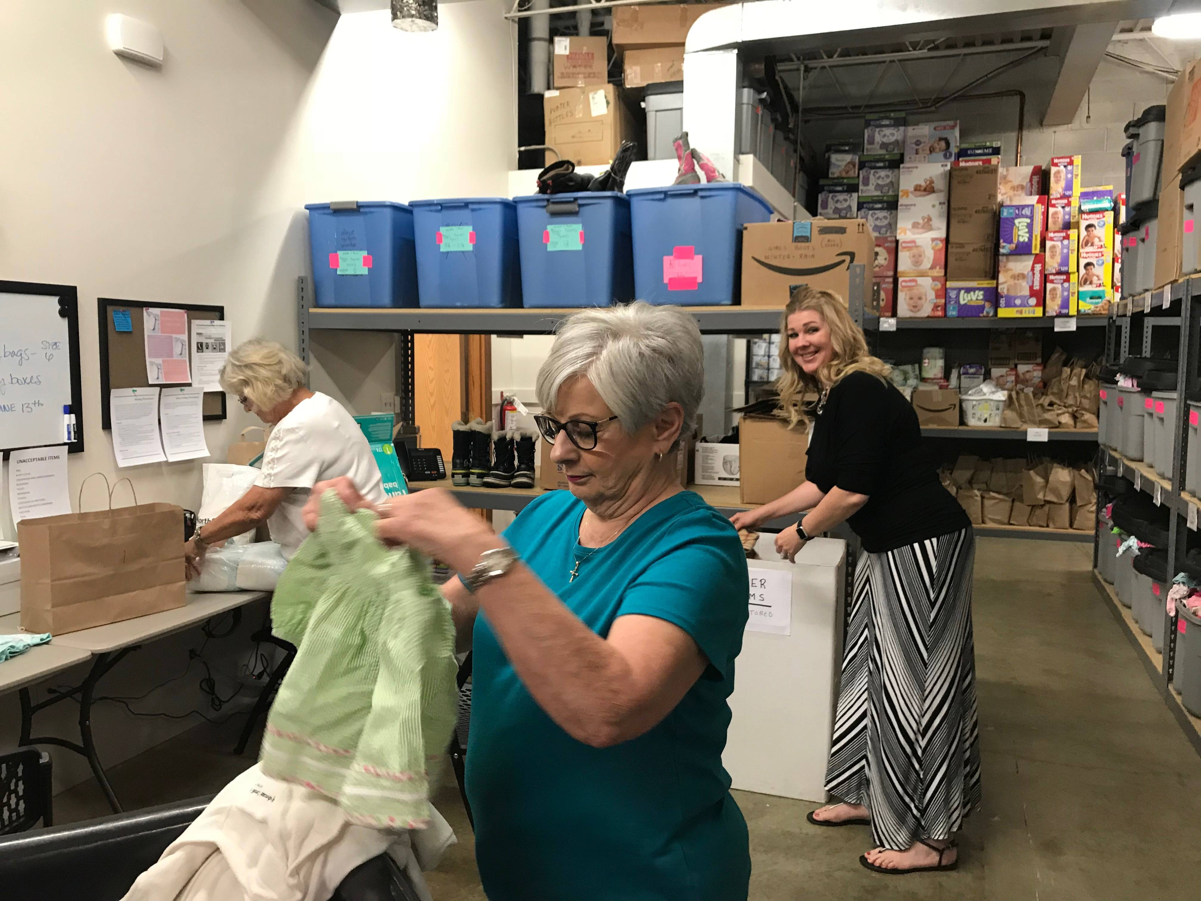 Volunteers Bunny Debevec, front, and Laura Dmytrenko, left, sort items of clothing in the storage room at the Twice As Nice Mother & Child facility on Grove Avenue in Gurnee as Ann Marie Mathis, founder of the nonprofit, checks out some of the latest donations.