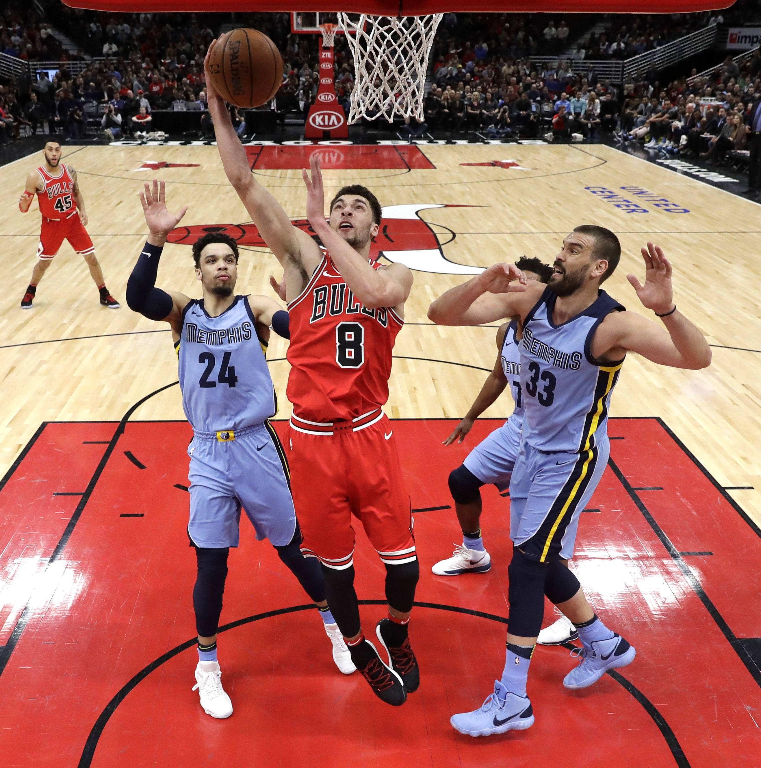 Chicago Bulls' Zach LaVine, center, scores between Memphis Grizzlies' Dillon Brooks, left,  and Marc Gasol, right, during the first half of an NBA basketball game Wednesday, March 7, 2018, in Chicago.