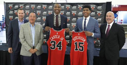 The Chicago Bulls first round draft picks, Wendell Carter Jr., (34) and Chandler Hutchison (15) pose with team executives from left, head coach Fred Hoiberg, general manager Gar Forman and executive vice president for basketball operations John Paxson, after a basketball news conference where they were introduced to Chicago reporters Monday, June 25, 2018, in Chicago.
