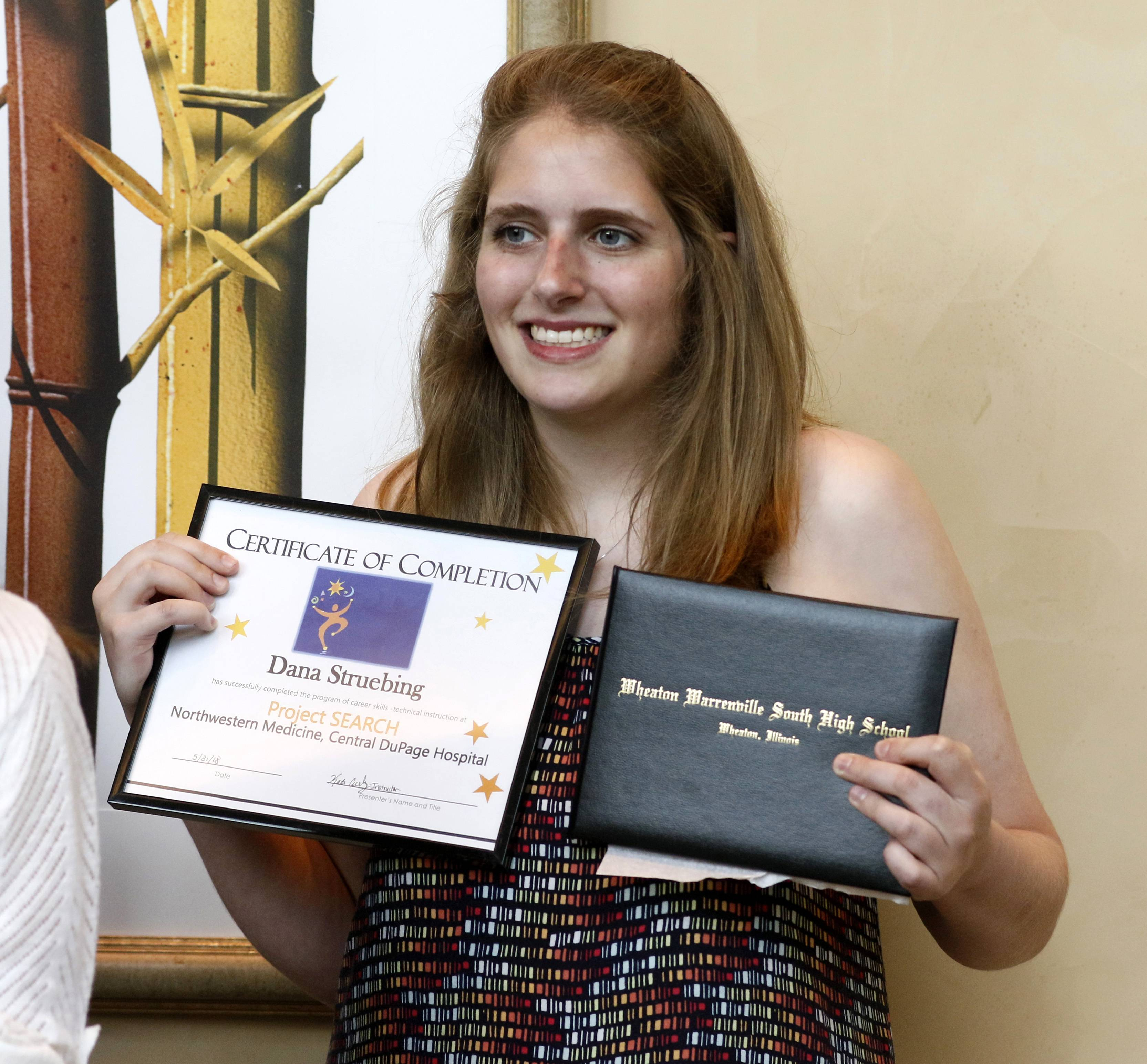 Dana Struebing shows off her Wheaton Warrenville South High School diploma and her certificate of completion after graduating from the Project SEARCH program at Northwestern Medicine Central DuPage Hospital in Winfield. The job training program aims to help students with special needs transition into the workforce.