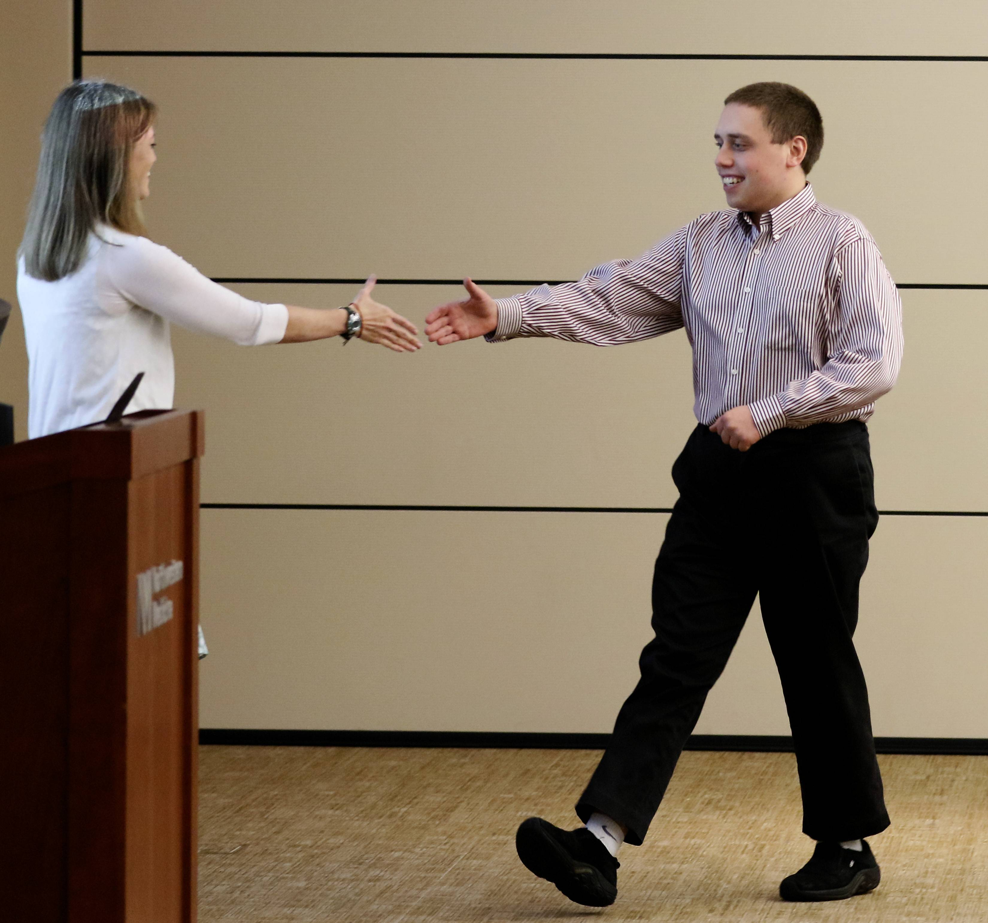Ben Sojka receives his certificate of completion at a ceremony at Central DuPage Hospital. Sojka, a Lisle 22-year-old who has autism, now works in a cafe at the Morton Arboretum.