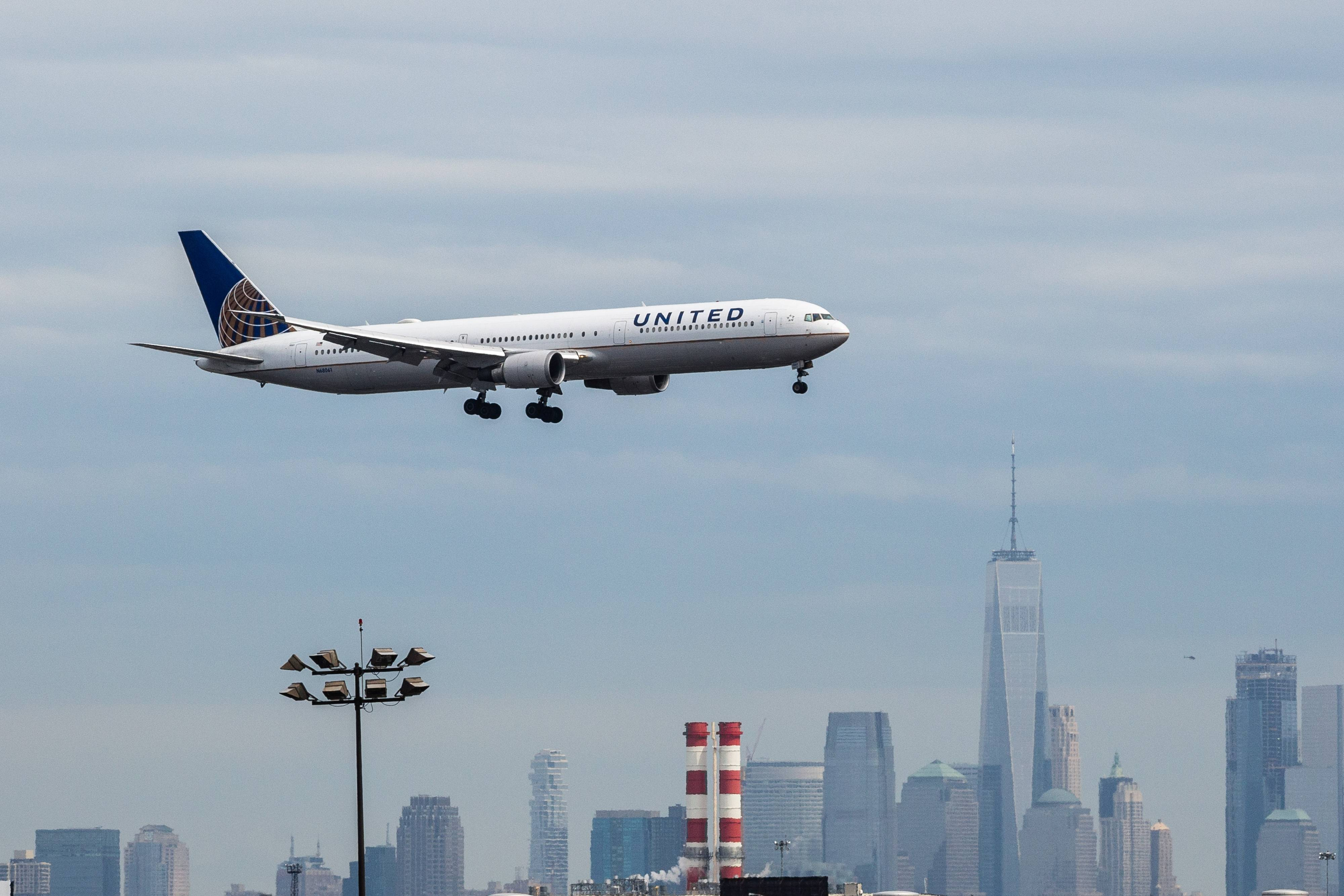A United passenger jet prepares to land as the New York City skyline stands in the background at Newark Liberty International Airport in Newark, N.J., on April 12, 2017. MUST CREDIT: Bloomberg photo by Timothy Fadek.