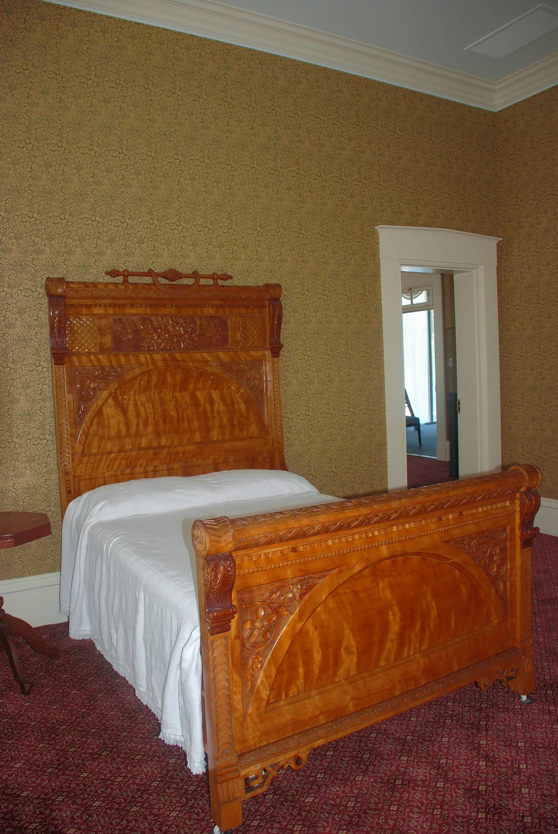 A farmer in Carthage carved bed and a matching furniture piece for Chicago's Columbian Exposition and then they were donated to the state while Gov. John Altgeld was in office (1893-1897). They now adorn a bedroom dedicated to the 1890s.