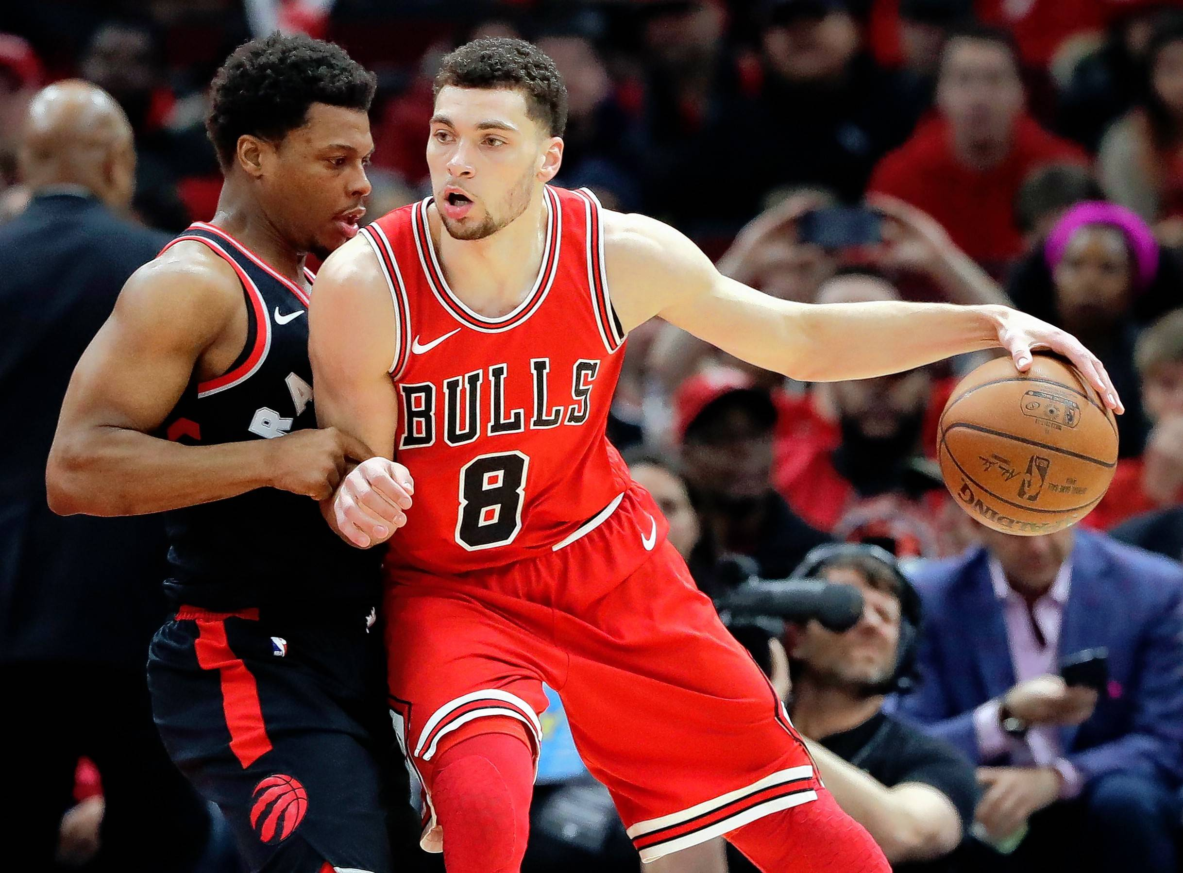 Chicago Bulls guard Zach LaVine, right, drives against Toronto Raptors guard Kyle Lowry during the first half of an NBA basketball game Wednesday, Feb. 14, 2018, in Chicago.