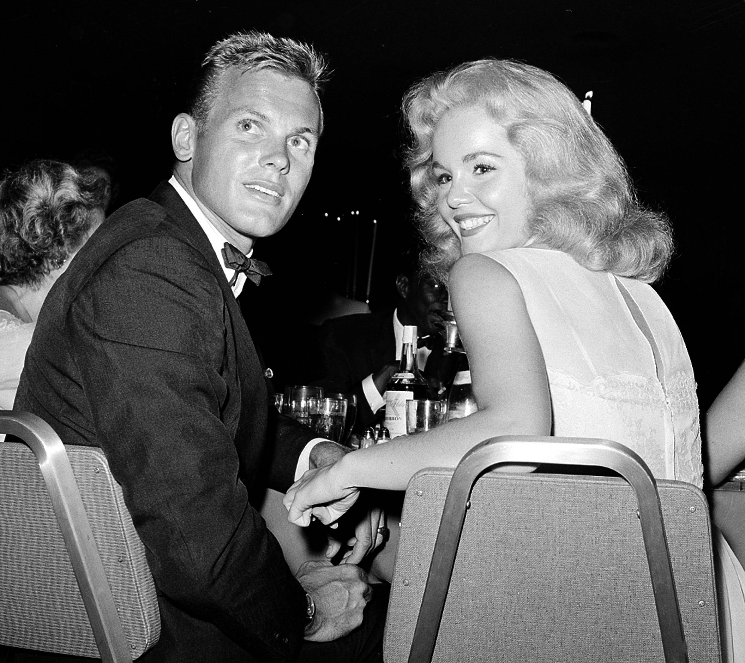 FILE - This July 27, 1959 file photo shows actor Tab Hunter, left, with actress Tuesday Weld at a dinner reception in Los Angeles. Hunter, the blond actor and singer who was the heartthrob of millions of teenage girls in the 1950s, and received new attention decades later when he revealed that he was gay, died on Sunday, July 8, 2018. He was 86.