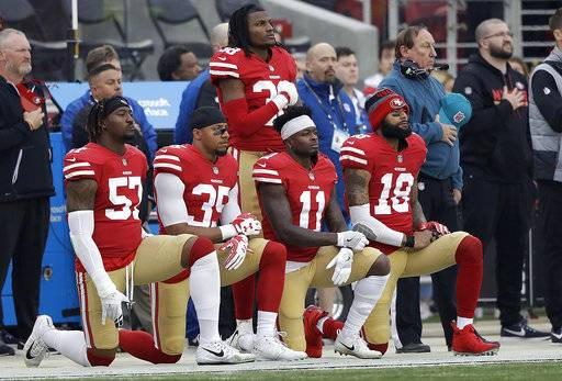 FILE - In this Dec. 24, 2017, file photo, San Francisco 49ers outside linebacker Eli Harold, from bottom left, kneels with safety Eric Reid, wide receiver Marquise Goodwin and wide receiver Louis Murphy during the national anthem before an NFL football game against the Jacksonville Jaguars in Santa Clara, Calif. The NFL Players Association filed a grievance with the league challenging its national anthem policy. The union says that the new policy, which the league imposed without consultation with the NFLPA, is inconsistent with the collective bargaining agreement and infringes on player rights.