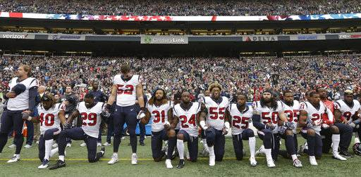 FILE - In this Oct. 29, 2017, file photo, Houston Texans players kneel and stand during the singing of the national anthem before an NFL football game against the Seattle Seahawks, in Seattle. The NFL Players Association filed a grievance with the league challenging its national anthem policy. The union says that the new policy, which the league imposed without consultation with the NFLPA, is inconsistent with the collective bargaining agreement and infringes on player rights.