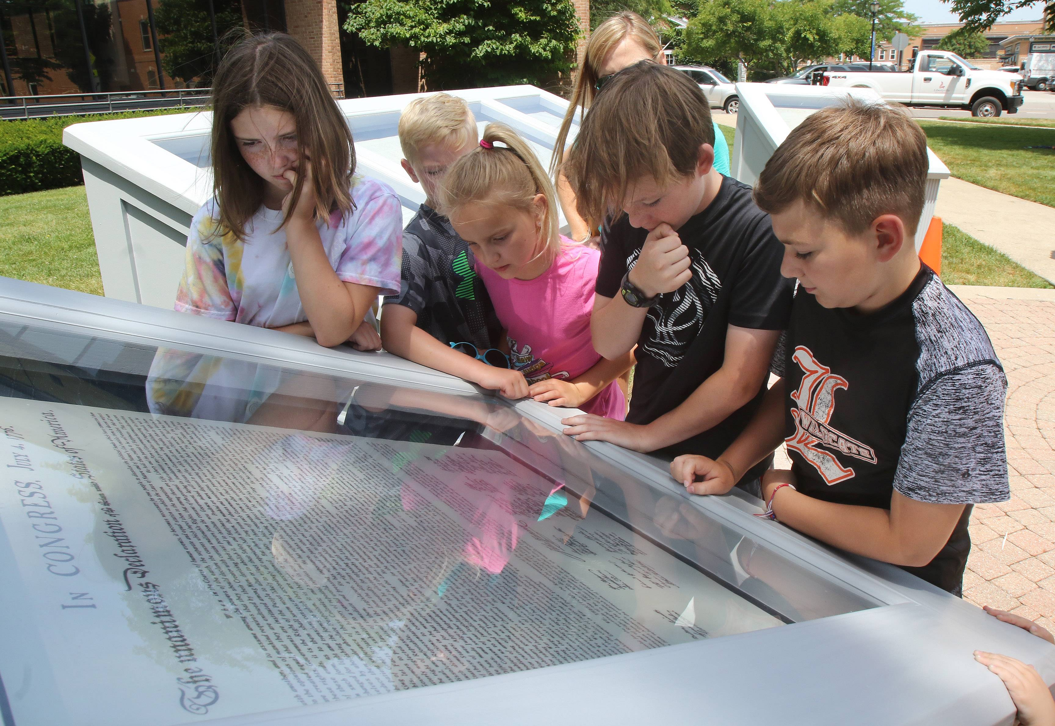 Jackson Groth, right, and Alex Brown, both 11 and from Libertyville, join other children to look at the Declaration of Independence after the Charters of Freedom exhibit was installed Wednesday at Cook Park in Libertyville.