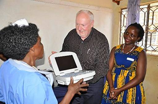 Deacon Don Grossnickle gives an ultrasound machine to a nurse at a clinic in Nakifuma, Uganda. Grossnickle is back from an eight-day medical mission to the African nation, where he saw signs of improvement, but also much work left to be done.