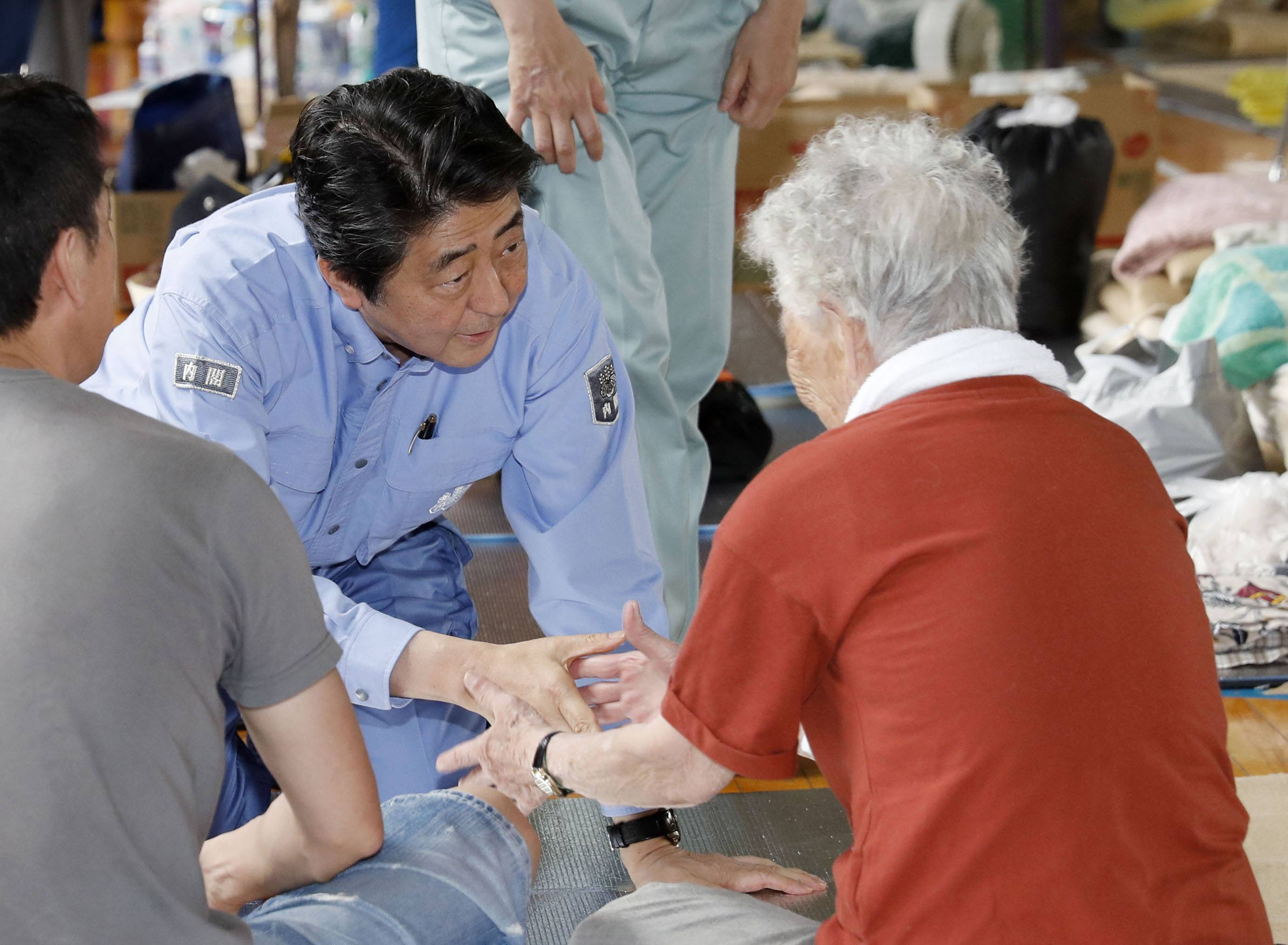 Japanese Prime Minister Shinzo Abe listens to an evacuee during a visit to an evacuation center in Kurashiki, Okayama prefecture, southwestern Japan, Wednesday, July 11, 2018. Abe visited the hard-hit city where a river broke through an embankment and swept through residential areas. (Shohei Miyano/Kyodo News via AP)