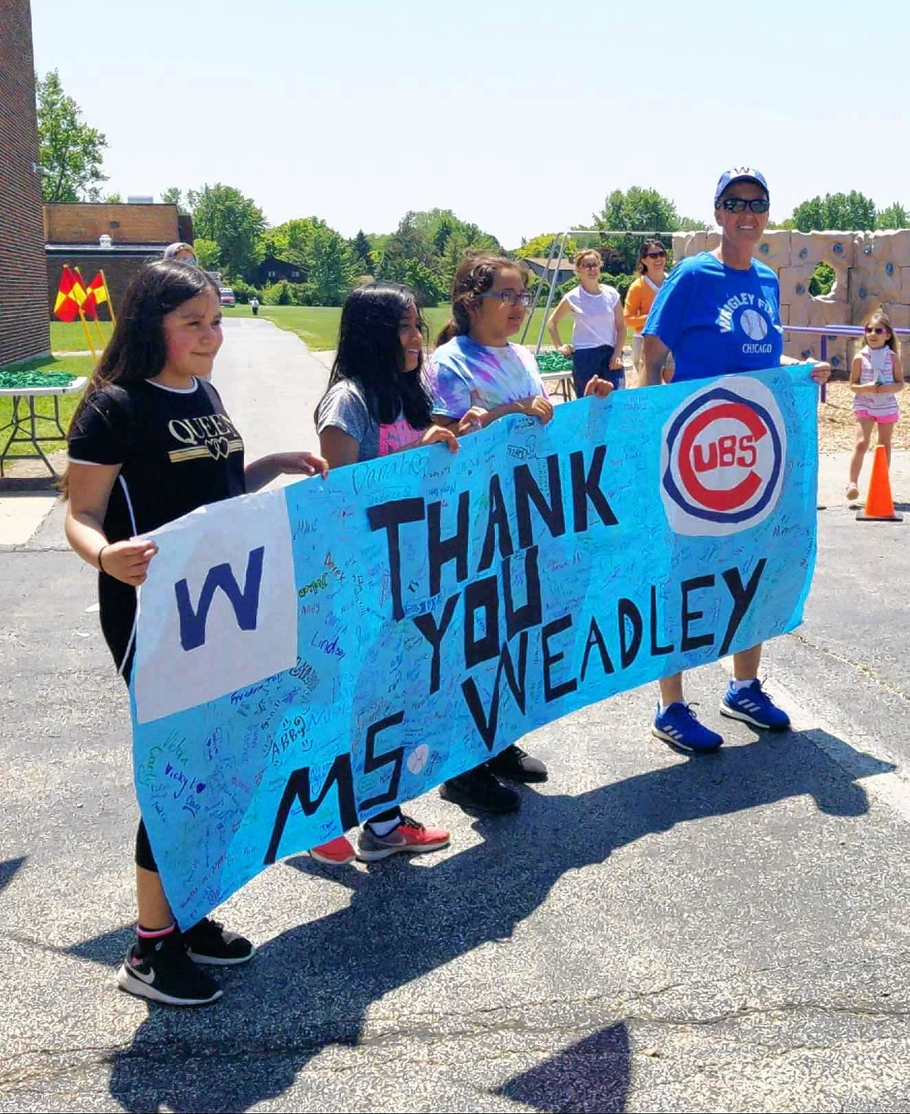 Anne Sullivan Elementary School students presented retiring physical education teacher Cathy Weadley with a banner signed by all 700 of this year's students. Weadley is retiring after 37 years with Prospect Heights Elementary District 23.