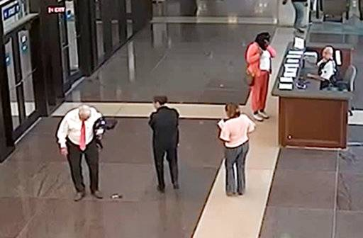 "In this July 3, 2018, photo from a surveillance video provided by the Cook County Sheriff's Office, Cook County Circuit Judge Joseph Claps, left, looks down at a gun he allegedly dropped in the lobby of the Leighton Criminal Court Building in Chicago. Claps has been charged with carrying a concealed weapon in a prohibited area and he has been reassigned to ""nonjudicial duties"" pending a review. (Cook County Sheriff's Office via AP)"
