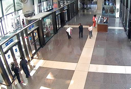 "This July 3, 2018, photo from a surveillance video provided by the Cook County Sheriff's Office shows Cook County Circuit Judge Joseph Claps reaching down to pick up a gun he allegedly dropped in the lobby of the Leighton Criminal Court Building in Chicago. Claps has been charged with carrying a concealed weapon in a prohibited area and he has been reassigned to ""nonjudicial duties"" pending a review. (Cook County Sheriff's Office via AP)"