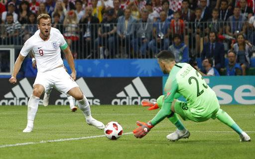 England's Harry Kane, left, plays the ball against the goal post during the semifinal match between Croatia and England at the 2018 soccer World Cup in the Luzhniki Stadium in Moscow, Russia, Wednesday, July 11, 2018.