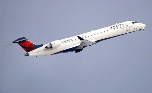 FILE- In this Jan. 8, 2018, file photo, a Delta Air Lines Connection regional jet operated by GoJet Airlines takes off from Logan International Airport in Boston. Delta Air Lines reports earns on Thursday, July 12.