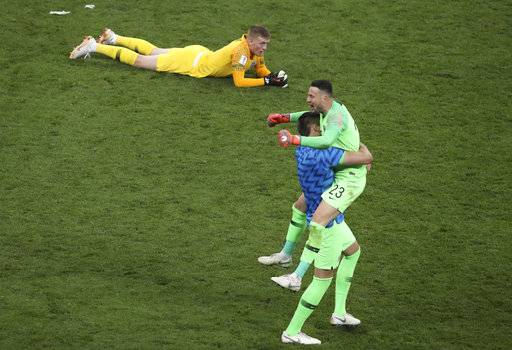 England goalkeeper Jordan Pickford lies down on the pitch as Croatia goalkeeper Danijel Subasic, right, celebrates at the end of the semifinal match between Croatia and England at the 2018 soccer World Cup in the Luzhniki Stadium in Moscow, Russia, Wednesday, July 11, 2018.