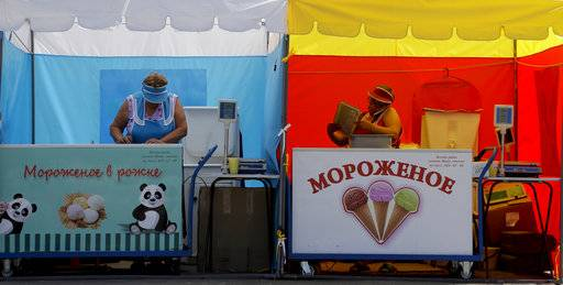 Two ice cream sellers prepare for business at their stand during the 2018 soccer World Cup in Nizhny Novgorod, Russia, Saturday, July 7, 2018.