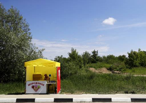 An ice cream seller waits for customers by the side of the road during the 2018 soccer World Cup at the in Nizhny Novgorod, Russia, Saturday, July 7, 2018.