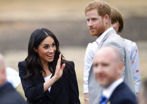 Prince Harry and Meghan Duchess of Sussex wave to members of the public at Trinity college, Dublin, Ireland, Wednesday, July 11, 2018.