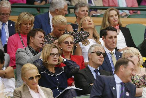 Britain's Cliff Richard, left, sits in the Royal Box on Centre Court ahead of the women's singles semifinal match between Angelique Kerber of Germany and Jelena Ostapenko of Latvia at the Wimbledon Tennis Championships, in London, Thursday July 12, 2018.