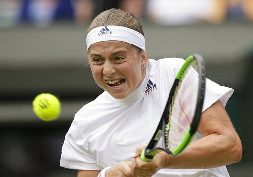 Jelena Ostapenko of Latvia returns the ball to Dominika Cibulkova of Slovakia during their women's quarterfinal match at the Wimbledon Tennis Championships in London, Tuesday July 10, 2018.