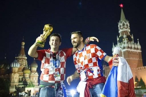 Croatia's soccer fans celebrate with a model of the World Cup trophy in Red Square as their team won the semifinal soccer match between Croatia and England during the 2018 soccer World Cup at the Luzhniki stadium in Moscow, Russia, early Thursday, July 12, 2018. The St. Basil's Cathedral is left and the Spasskaya Tower is right in the background.