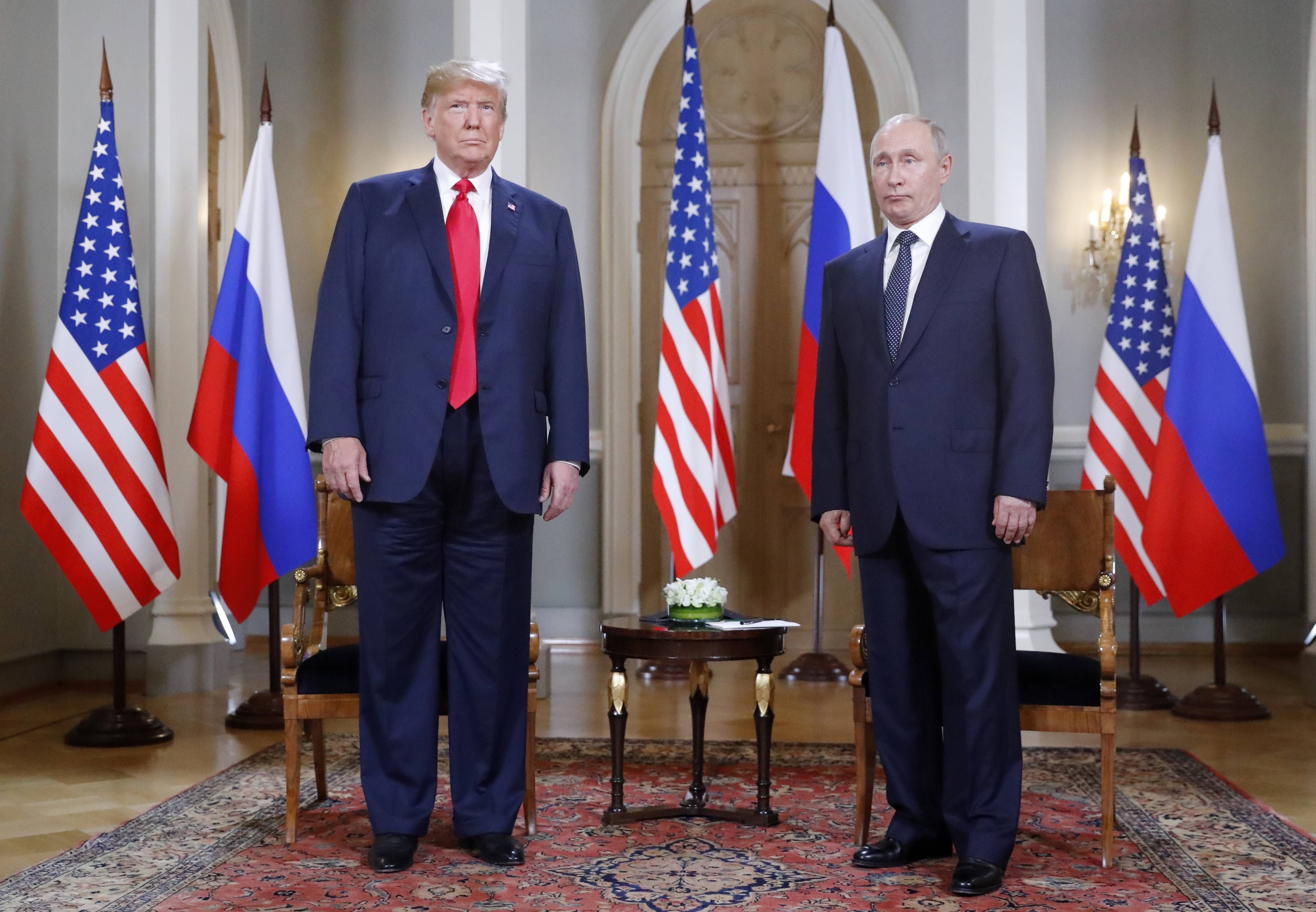 U.S. President Donald Trump, left, and Russian President Vladimir Putin pose for a photograph at the beginning of a one-on-one meeting at the Presidential Palace in Helsinki, Finland, Monday.