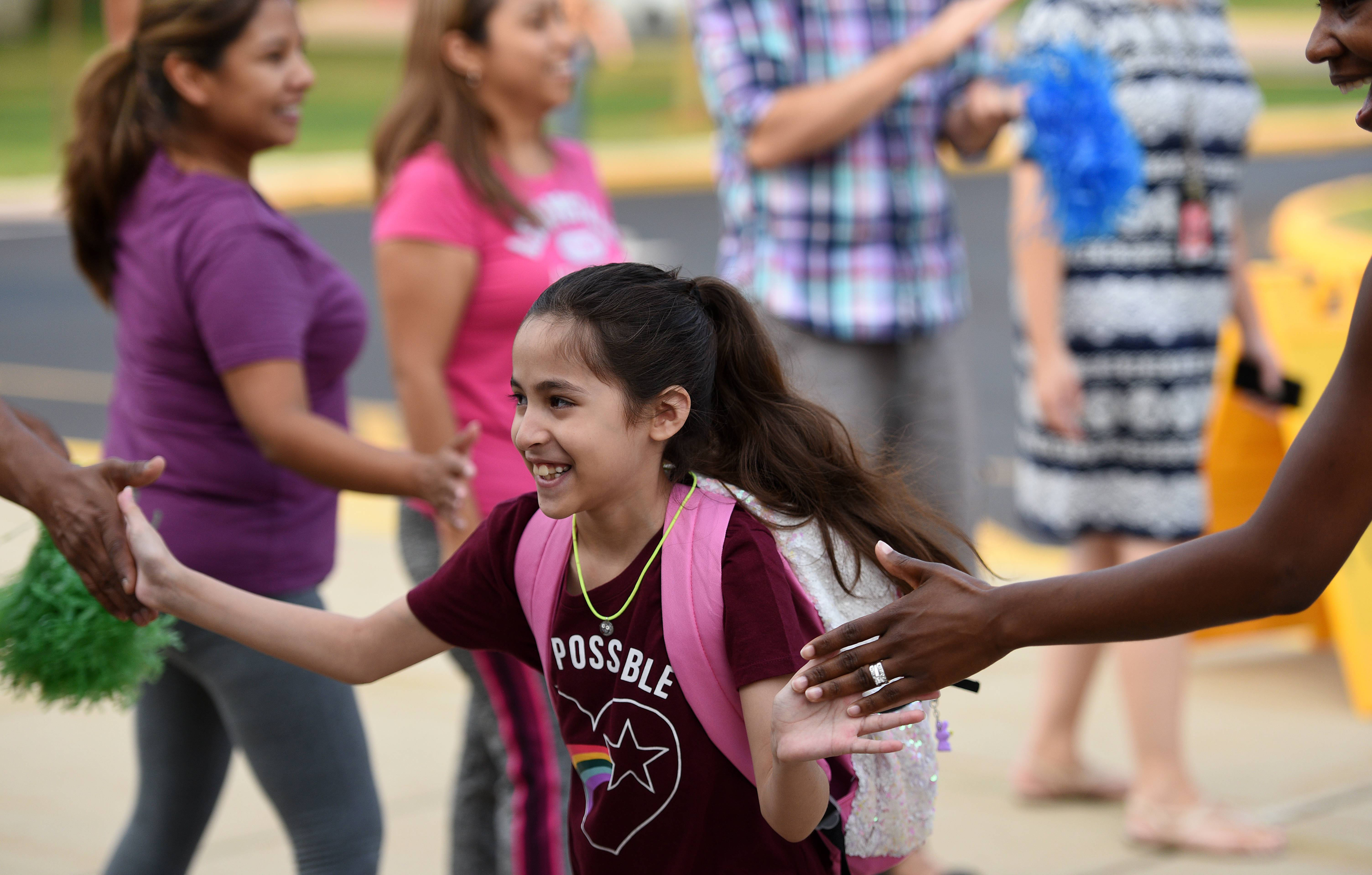 Jamile Adela gives fives as she arrives for her first day of fourth grade at Golfview Elementary School in Carpentersville. It was the first day for students throughout Community Unit District 300.