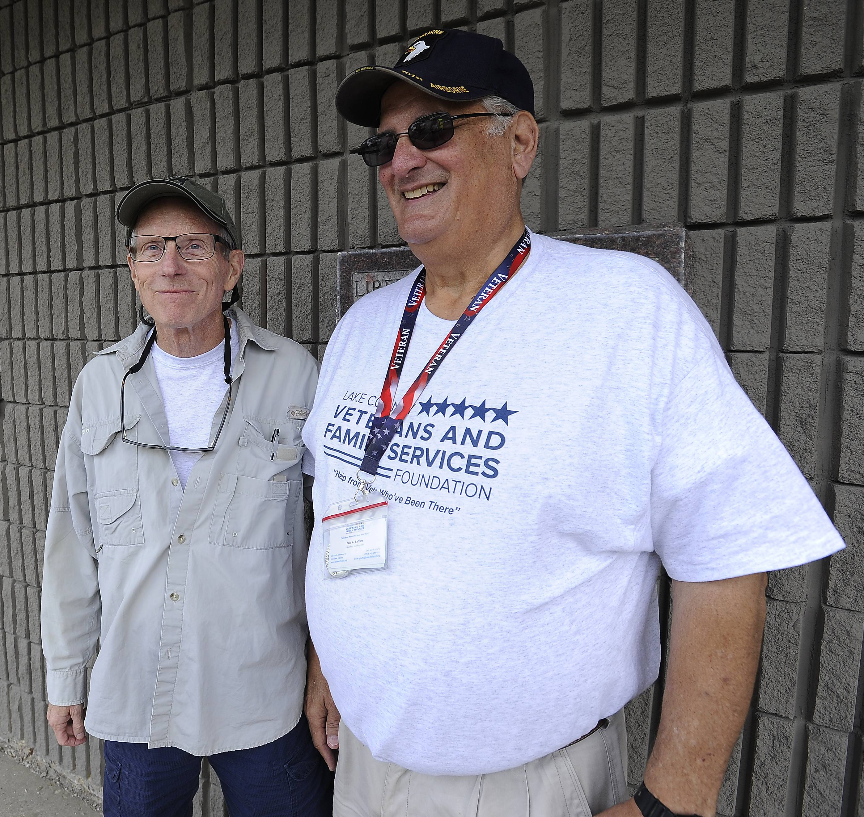 Bob Gorman of Barrington, left, and Paul Baffico of Lake Bluff, watch Saturday as more than 85 supporters of the Lake County Veterans Family Services Foundation begin a march to bring awareness to the community that 20 veterans kill themselves a day around the country.