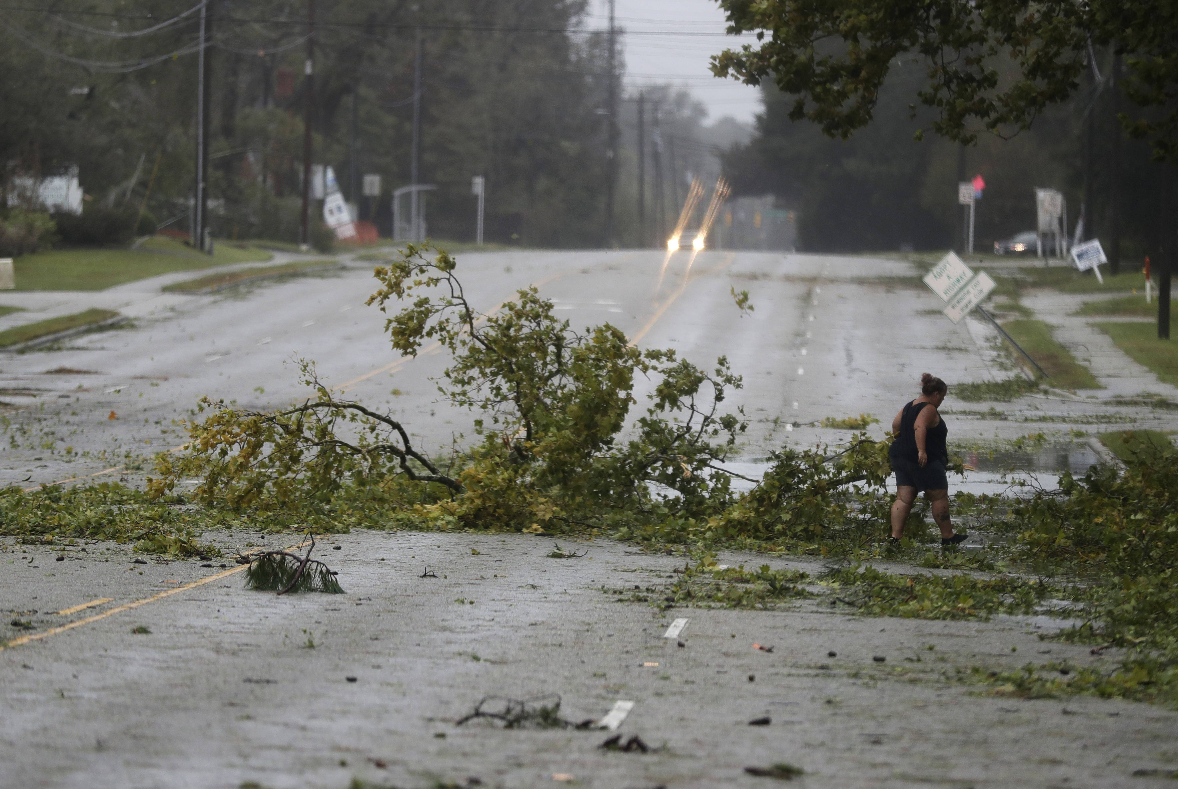 A woman removes debris from a road in Wilmington, N.C., after Hurricane Florence made landfall Friday, Sept. 14, 2018.
