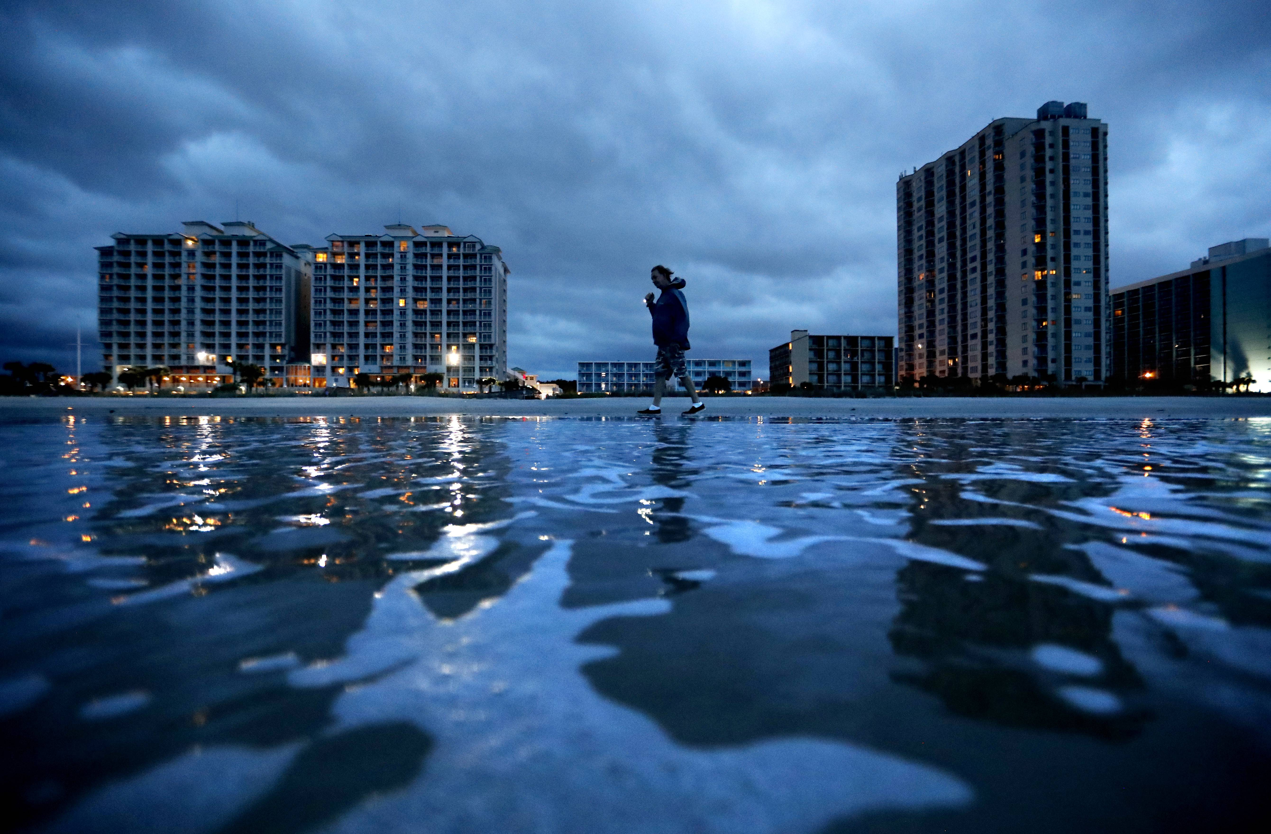 "Russ Lewis looks for shells along the beach as Hurricane Florence approaches Myrtle Beach, S.C., Friday, Sept. 14, 2018. ""We might get lucky we might not we'll find out,"" said Lewis of the storm."
