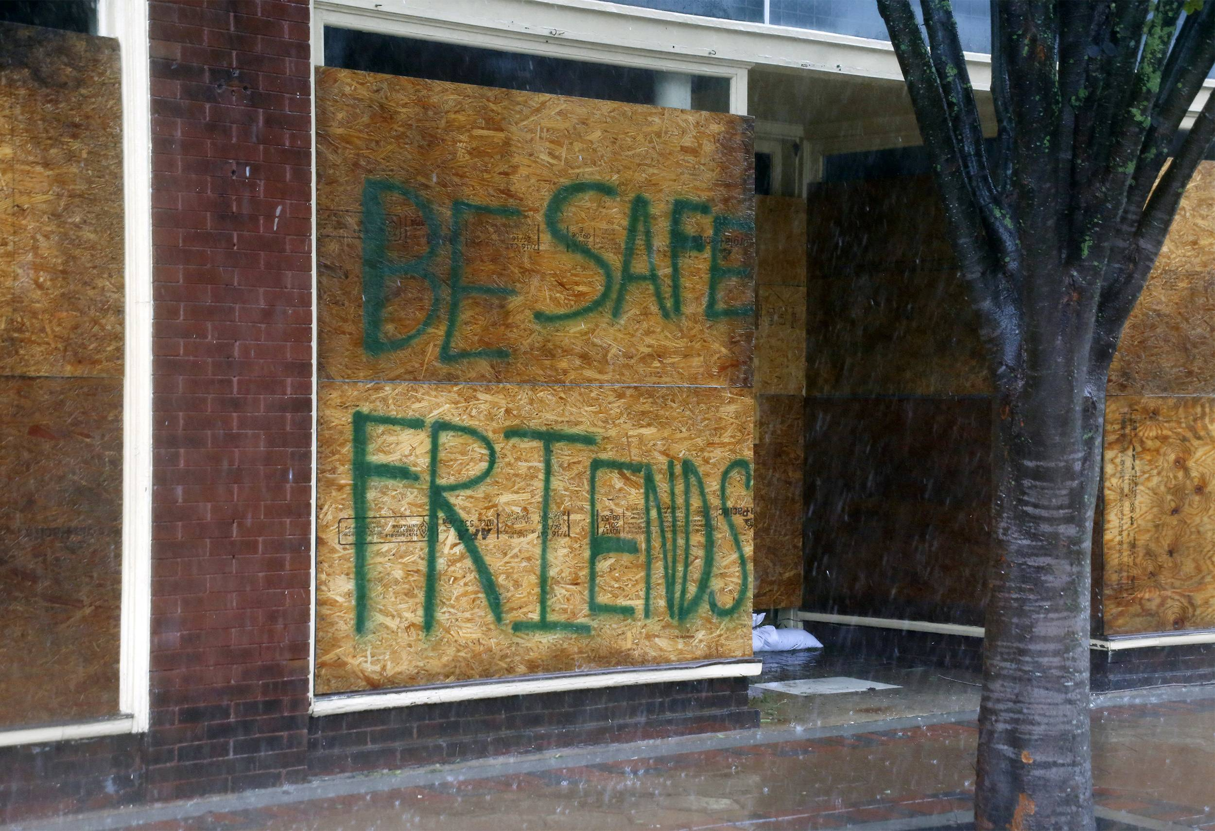 A message on a boarded-up business encourages people to be safe as Hurricane Florence hits downtown New Bern, N.C., on Friday, Sept. 14, 2018.