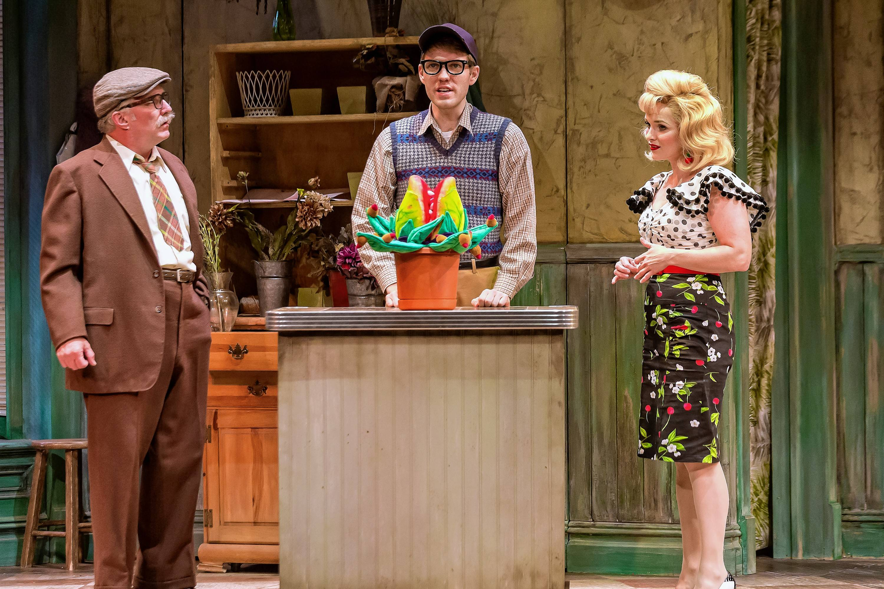 "Mr. Mushnik (Ron E. Rains), left, Seymour (Will Lidke) and Audrey (Kelly Felthous) marvel over the new exotic plant in ""Little Shop of Horrors"" at Drury Lane Theatre in Oakbrook Terrace."