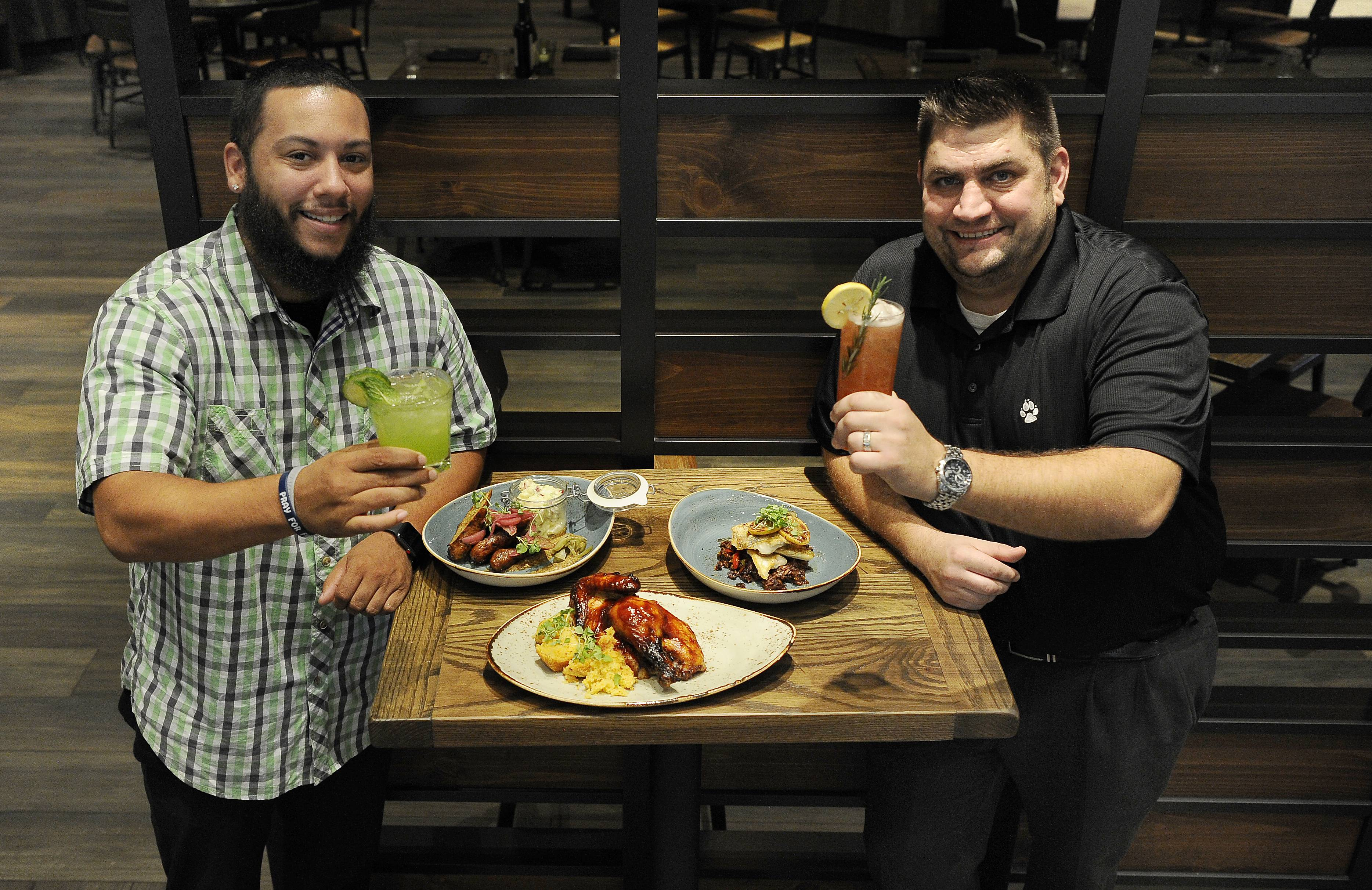 Alejandro Rodriguez, left, bartender and server, and Jake Kitzerow, food and beverage manager, show off some of the hearty dishes at Barnwood in the Great Wolf Lodge in Gurnee.