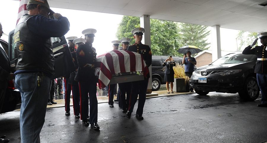 Arriving under the escort of a police motorcade, the remains of Harry Carlsen, a World War II sergeant killed in action in 1943, made it to Arlington Heights Wednesday. The Marine unit carried Carlsen's casket into the funeral home where family members awaited.