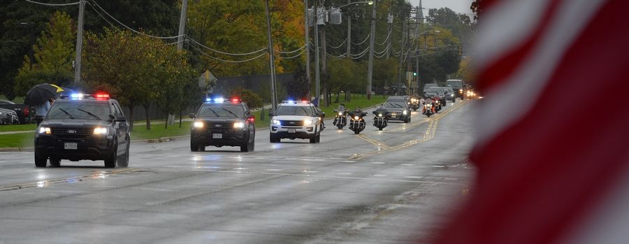 A police motorcade escorting the body of Harry Carlsen, a World War II sergeant killed in action in 1943, heads up Arlington Heights Road Wednesday.