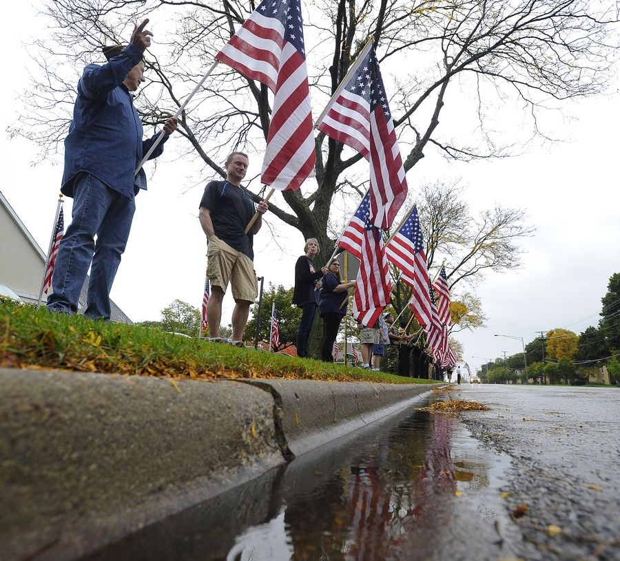 A police motorcade escorting the body of Harry Carlsen, a World War II sergeant killed in action in 1943, made its way up Arlington Heights Road to the funeral home where it was met by a line of veterans with flags.