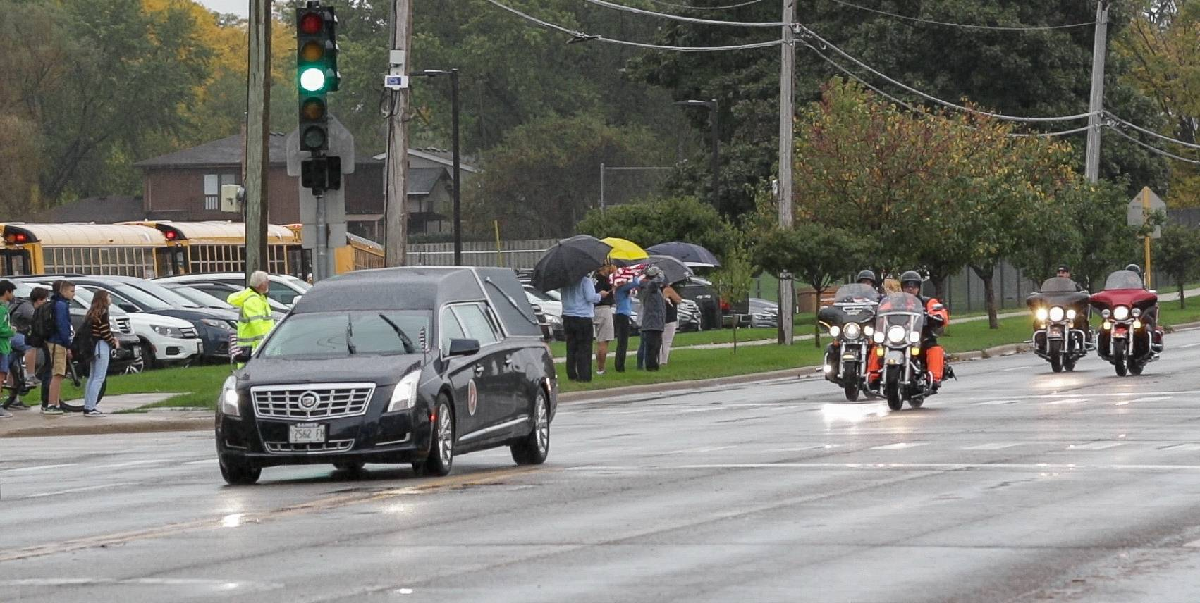A police motorcade escorting the remains of Harry Carlsen, a World War II technical sergeant killed in action on Nov. 20, 1943, makes its way down Arlington Heights Road Wednesday in Arlington Heights.